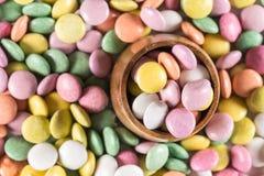 Caramelos redondos coloridos en la taza de madera Fotos de archivo