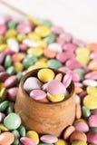 Caramelos redondos coloridos en la taza de madera Fotografía de archivo libre de regalías