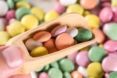 Caramelos redondos coloridos macros del primer con la cuchara de madera Fotos de archivo