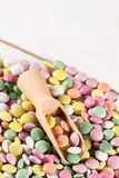 Caramelos redondos coloridos macros del primer con la cuchara de madera Imagenes de archivo