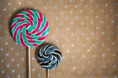 Caramelos redondos sabrosos en el palillo de madera en fondo del arte de papel con las estrellas Copie el espacio para el texto y Fotos de archivo libres de regalías