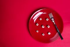 Caramelos rojos de los corazones en la placa roja Foto de archivo