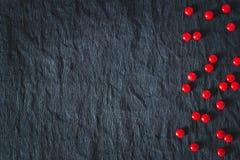 Caramelos rojos en bacground negro Imagen de archivo libre de regalías