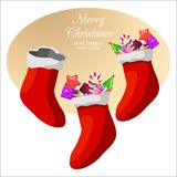 Caramelos y dulces de la Navidad en calcetines de la Navidad Imagenes de archivo