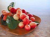 Carandas или karonda Carissa белы и красны с зелеными листьями в деревянных плитах На старой деревянной таблице это малый плодоов Стоковое фото RF