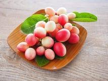 Carandas или karonda Carissa белы и красны с зелеными листьями в деревянных плитах На старой деревянной таблице это малый плодоов Стоковое Изображение