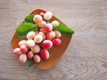 Carandas или karonda Carissa белы и красны с зелеными листьями в деревянных плитах На старой деревянной таблице это малый плодоов Стоковые Фотографии RF