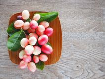 Carandas или karonda Carissa белы и красны с зелеными листьями в деревянных плитах На старой деревянной таблице это малый плодоов Стоковая Фотография