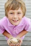 Caranguejo novo da terra arrendada do menino na praia Imagens de Stock Royalty Free