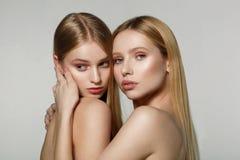 Caras bonitas novas de duas meninas adultas com os ombros desencapados no fundo cinzento fotografia de stock royalty free
