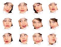 Caras de la muchacha en un agujero de papel Fotos de archivo
