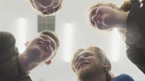 Caras de la situación que habla de cuatro personas en el círculo sobre la cámara Una compañía de los atletas de sexo masculino y  almacen de video