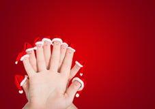 Caras de los fingeres en los sombreros de Papá Noel contra fondo rojo Foto de archivo libre de regalías