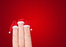 Caras de los fingeres en los sombreros de Papá Noel contra fondo rojo Fotografía de archivo libre de regalías