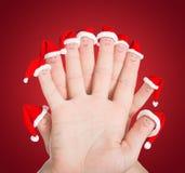 Caras de los fingeres en los sombreros de Papá Noel contra fondo rojo Concepto para Fotografía de archivo