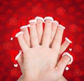 Caras de los fingeres en los sombreros de Papá Noel contra fondo rojo de los copos de nieve C Foto de archivo