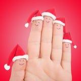 Caras de los fingeres en los sombreros de Papá Noel Familia feliz que celebra concepto Imagen de archivo