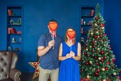 Caras de ocultación de los pares jovenes detrás de las cajas en forma de corazón rojas en la decoración de la Navidad en casa fotografía de archivo libre de regalías