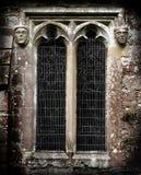 Caras de piedra góticas al lado de una ventana de la iglesia Imagen de archivo