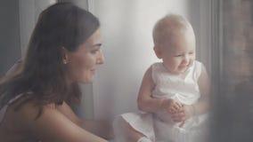 Caras de riso da família feliz, mãe que guarda o bebê adorável da criança, sorrindo e abraçando, beira ascendente próxima, beleza Fotografia de Stock