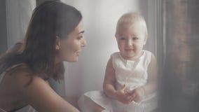 Caras de riso da família feliz, mãe que guarda o bebê adorável da criança, sorrindo e abraçando, beira ascendente próxima, beleza Fotografia de Stock Royalty Free