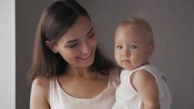Caras de riso da família feliz, mãe que guarda o bebê adorável da criança, sorrindo e abraçando, beira ascendente próxima, beleza Imagem de Stock
