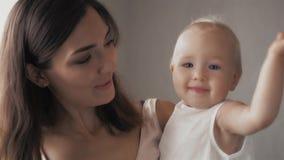 Caras de riso da família feliz, mãe que guarda o bebê adorável da criança, sorrindo e abraçando, beira ascendente próxima, beleza Imagens de Stock