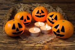 Caras divertidas pintadas en las mandarinas alrededor de las velas encendidas para Halloween fotos de archivo libres de regalías
