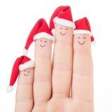 Caras dos dedos em chapéus de Santa Família feliz que comemora o conceito Imagens de Stock Royalty Free