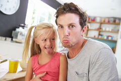 Caras engraçadas de And Daughter Making do pai na tabela de café da manhã Imagens de Stock