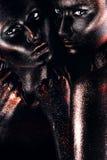 Caras y hombro de las mujeres en pintura negra Foto de archivo libre de regalías