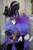 Carattere di carnevale di Venezia in un costume variopinto di carnevale ed in una maschera porpora e neri Venezia Immagine Stock Libera da Diritti