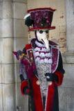 Carattere di carnevale di Venezia in un costume variopinto di carnevale ed in una maschera rossi e neri Venezia Immagine Stock