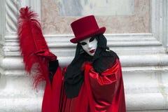 Carattere di carnevale di Venezia in un costume variopinto di carnevale ed in una maschera rossi e neri Venezia Fotografie Stock