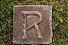 Carattere in grassetto R in terra Fotografia Stock