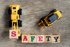 Carattere in grassetto s del bulldozer del giocattolo del giocattolo di plastica della tenuta per esprimere sicurezza Immagini Stock