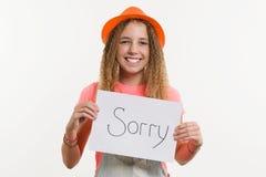 Carattere teenager sveglio della ragazza che giudica un segno con il messaggio spiacente fotografia stock