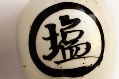 Caratteri giapponesi neri sul vecchio barattolo ceramico fotografie stock libere da diritti