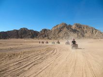 Caravan ATV racing at high speed through the desert raising dust royalty free stock photography