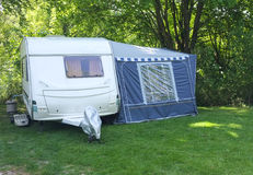 Caravan and Awning, Woodland Camping. A family caravan and awning set up on a pitch in woodland trees on grass. Blue full awning on the side of a white royalty free stock image