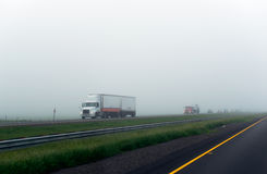 Caravan of big rigs semi trucks on the foggy highway. Big rig semi truck with double trailers moves ahead of the column of cars on a split road with poor royalty free stock photos