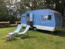 Caravan blu d'annata, sdrai e tavole su erba Immagine Stock Libera da Diritti