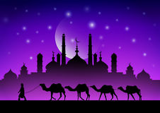Caravan of camels in the desert near the mosque under the moon. Abstract Royalty Free Stock Photo