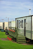 Caravan camp on green grass under clouds. Illustration of caravan camp or trailer park, decorated with flower beds, taken near Skipsea, Driffield, UK Royalty Free Stock Photo