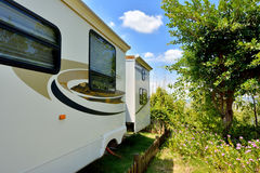 Caravan in camp. Travel trailer in beautiful camp with tree and flower, shown as enjoy wonderful trip and holiday, or featured living environment Royalty Free Stock Photos