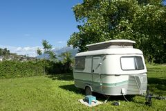 Caravan at camping. Small caravan at a camping with at background mountains with snow stock image