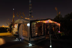 Caravan on campsite. Illuminated in the evening royalty free stock photo