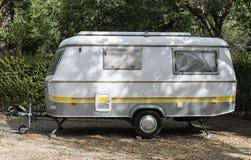 Caravan on campsite. Small caravan on campsite. Green bushes royalty free stock photography