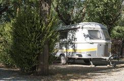 Caravan on campsite. Small caravan on campsite. Green bushes stock photos