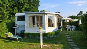 Caravan con una veranda fissa fatta del tessuto della tenda, delle finestre di scivolamento di vetro e dei ciechi su un campeggio immagine stock